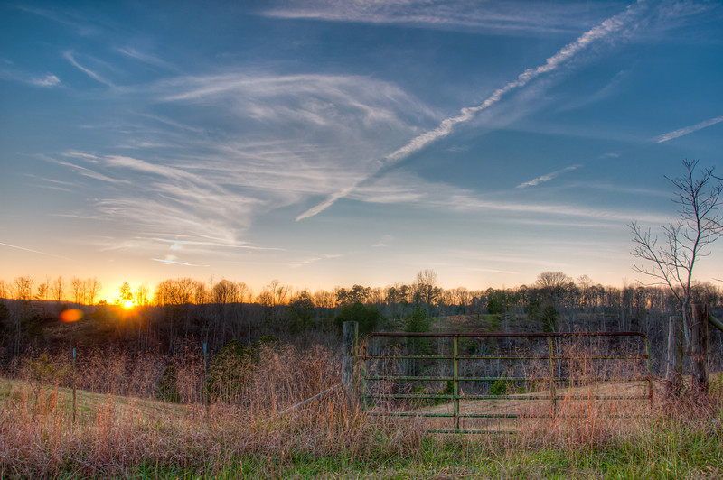 "<h3><strong>Today's Photo:  North Georgia Sunset</strong></h3> For me there is something magical about seeing the moment when the sun first appears or begins to set.  Whenever I am out at this time of day, whether it is morning or evening, I try to stop and just enjoy it.  Some of the time I actually make it there with a camera.  Of course it would not be a classic without the gate.  Read more at the <a href=""http://justshootingmemories.com"" rel=""nofollow"">Daily Photography Blog</a> Just Shooting Memories!..."