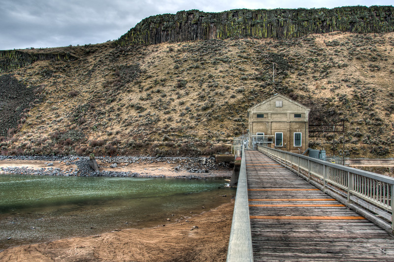 """<h3 style=""""text-align: left;""""><strong>Today's Photo:  Boise River Diversion Dam</strong></h3> Looking at photos from the Northwest United States, most of them you see are of green forests, vast rivers and tall mountains.  Rarely do you see the dry, barren high deserts.  That was one of the first things I experienced in Boise.  There are mountains, big mountains and very close, but Boise itself and the immediate surrounding area is high desert.  Through the ingenuity of the early settlers to this area, the ability to live and thrive was derived from the Boise River.  Just as the river flows from the surrounding mountains, a diversion dam was constructed to irrigate the Boise valley.  This is the dam where the water is separated into the irrigation canal and the Boise River.  Read more at the <a href=""""http://justshootingmemories.com"""">Daily Photography Blog</a> Just Shooting Memories!..."""