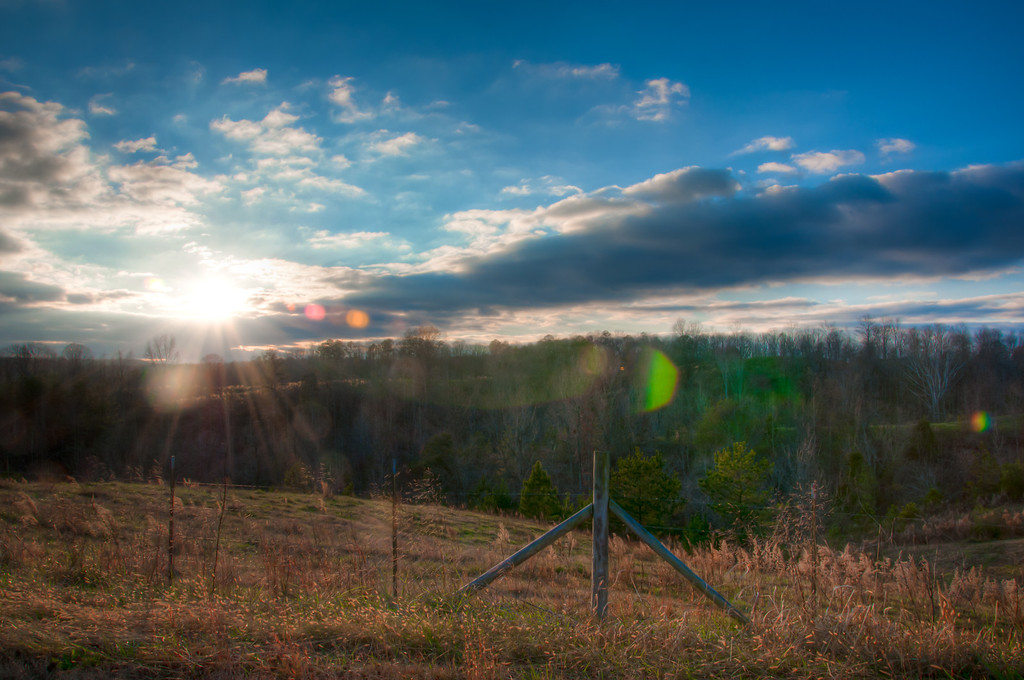 "<h3><strong>Today's Photo:  Almost There</strong></h3> Sunrise and sunset are two favorite times for me to take photos, along with almost every other photographer out there.  The reason is the quality of light.  That leads to all kinds of interesting discussions.  I got this shot along one of my country roads around the beginning of that magical time around sunset.  One of the best things about shooting HDR is the ability to shoot into the sun and still get a good overall exposure.  It also can give you some really good lens flare effects.  Read more at the <a href=""http://justshootingmemories.com"">Daily Photography Blog</a> Just Shooting Memories!..."