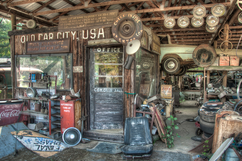 """<h3 style=""""text-align: left;""""><strong>Today's Photo:  The Office</strong></h3> <strong></strong>I have shared many photos from my time at Old Car City USA.  I was going through them the other day and noticed that I had not shared any of the facilities.  The majority have been of vehicles.  There are several buildings around the junkyard, but this one used to be the old office.  I liked all the hand painted signs and then near the back of this building there were cars just suspended like they were on a lift.  It was obvious that at one point in time, this was the center of the yard."""