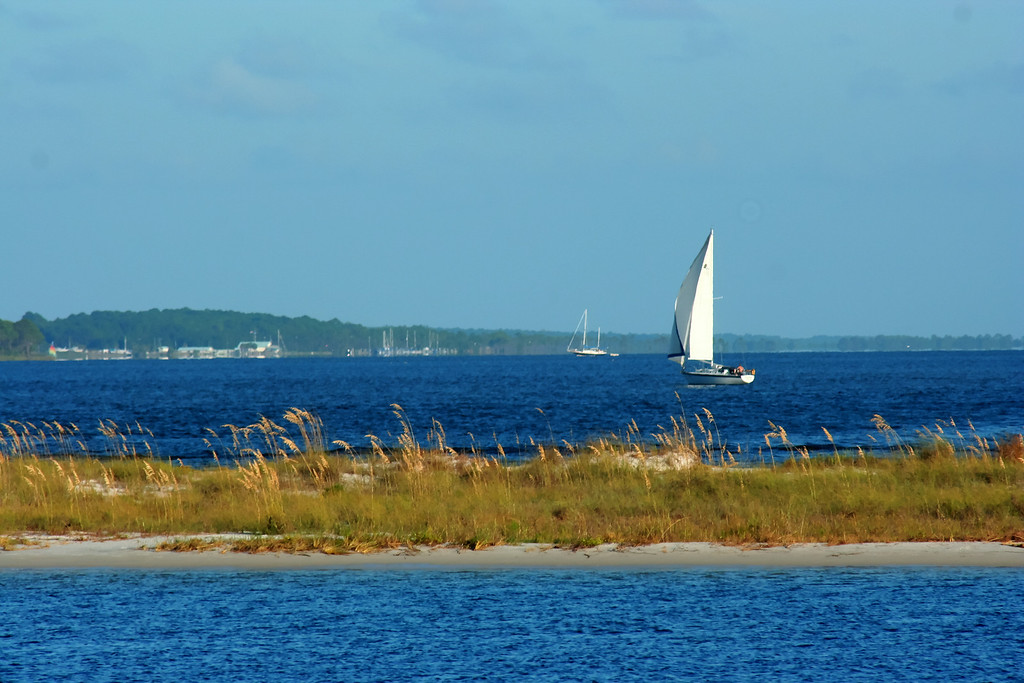 "<h3><strong>Today's Photo:  A Lone Sail</strong></h3> I have always loved the water.  I try to make it to the beach at least once a year.  That always does not happen.  The family and I rode the Shell Island dolphin cruise one year in Panama City Beach, Florida.  There is a nice little cruise in the coastal waterway and then through the pass and a short way into the ocean.  There is one area just before entering the pass that you go through a channel that has to be only 15 - 20 feet wide.  This was shot across the small peninsula and into the pass.  Read more at the <a href=""http://justshootingmemories.com"">Daily Photography Blog</a> Just Shooting Memories!..."
