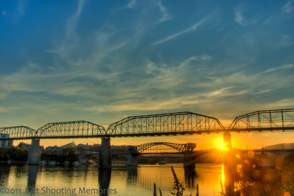 """<h3><strong>Today's Photo: Chattanooga Sunset</strong></h3> I took this shot of the Chattanooga skyline at sunset in October. A few minutes later, I got another shot of the <a title=""""Chattanooga Skyline at Dusk"""" href=""""http://justshootingmemories.com/2011/10/11/chattanooga-skyline-at-dusk/"""">Chattanooga Skyline at Dusk</a>. It is amazing how much just a few minutes can change the way a complete scene looks. From warm tones to cold, the golden hour or blue hour can be quite exciting and a mad dash for just the right spot. Luckily, I set up for this shot about 45 minutes before sunset, laid back on the grass, relaxed and listened to some tunes. When I first set the tripod up, there was no one there. About 10 minutes before sunset, I had about 10 couples who gathered in the area to watch the sunset. From the angle of the sunset, I can imagine this attracts a lot of couples to enjoy a pleasant evening.  Read more at the <a href=""""http://justshootingmemories.com"""">Daily Photography Blog</a> Just Shooting Memories!..."""