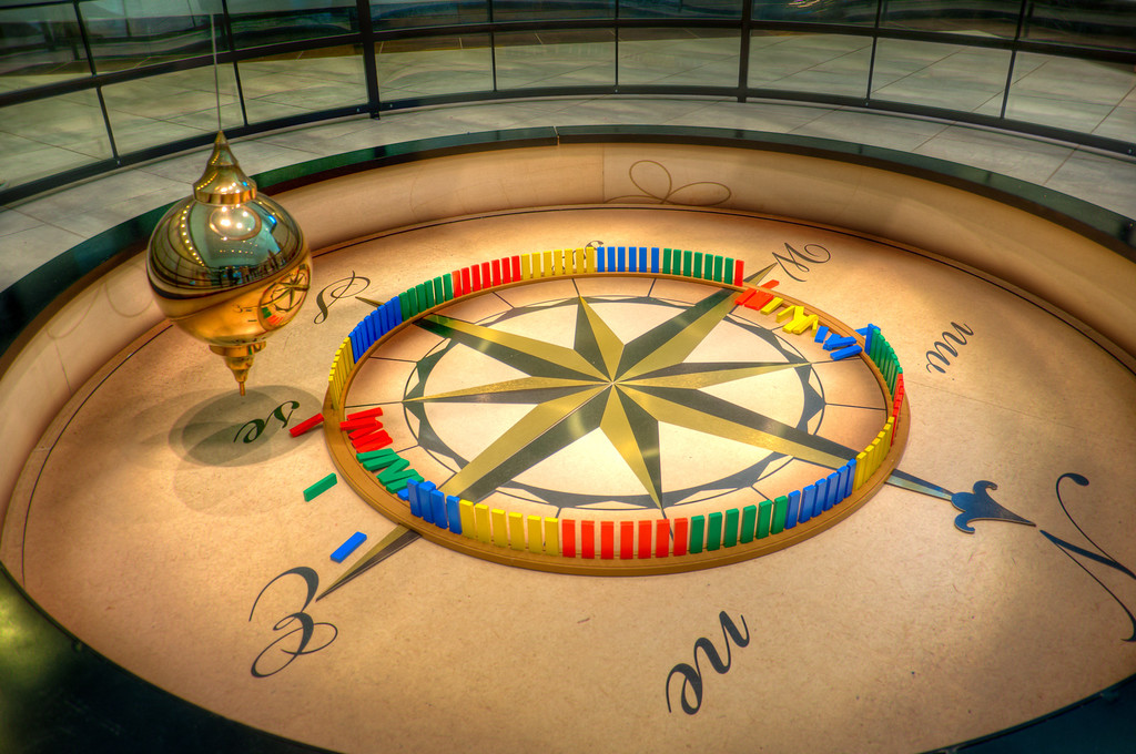 "<h3><strong>Today's Photo: Foucault Pendulum</strong></h3> I have seen these in several places before and I can still watch them for hours, if I have the time.  This is called a <a title=""Foucault Pendulum on Wikipedia"" href=""http://en.wikipedia.org/wiki/Foucault_pendulum"" target=""_blank"">Foucault Pendulum</a> and swings with the rotation of the earth.  The blocks around the outside get knocked over as it moves around the circle.  I was lucky enough to make it by this one just before one of the blocks got knocked over.  It fell to the outside, which does not happen often.  As you can see here, only five of the twenty nine made it to the outside.  For it to fall outside the circle, it gets grazed just barely and begins rocking until the next swing brings it crashing down.  Getting the three shots for an HDR was challenging for this one considering I was not using a tripod.  Read more at the <a href=""http://justshootingmemories.com"">Daily Photography Blog</a> Just Shooting Memories!..."