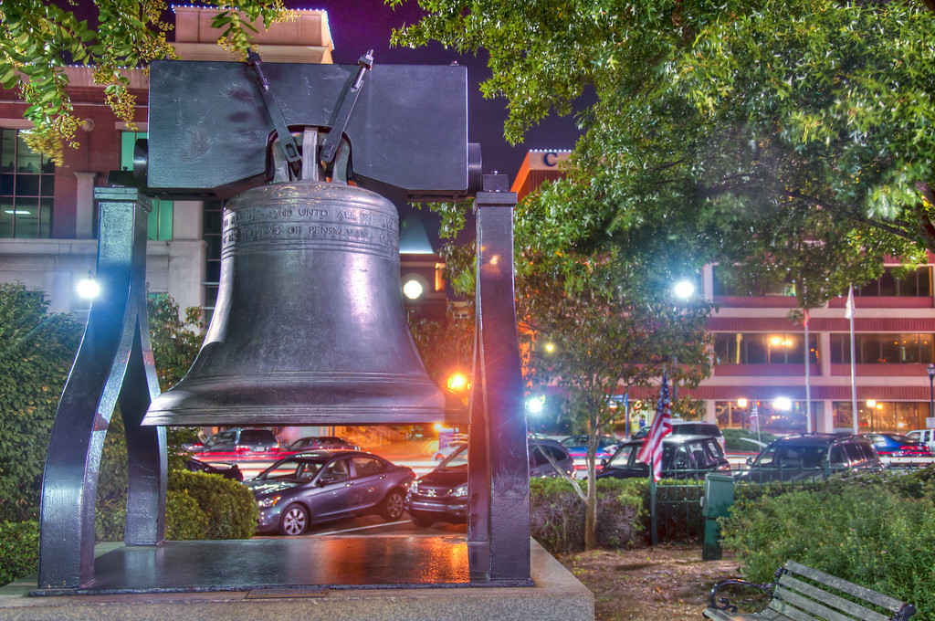 "<h3><strong>Today's Photo:  Liberty Bell</strong></h3> I spent a lot of time on the square in Marietta, Georgia, growing up.  It has changed a lot since then, but it is still the same.  Have you ever felt that way about some place?  I played on the train which is set up as a slide and for the kids to play on.  It was pretty neat to watch my children playing there also.  One of the things I did not remember was the Liberty Bell which is along the east side of the park.  It made for some great night time shots.  I was just glad the wind stopped for just a second that I could get the flag too.  Read more at the <a href=""http://justshootingmemories.com"">Daily Photography Blog</a> Just Shooting Memories!..."