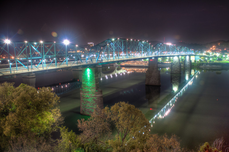 """<h3 style=""""text-align: left;""""><strong>Today's Photo:  Walnut Street Bridge at Night</strong></h3> Part of the reason I like Chattanooga Tennessee so much are the bridges.  All of them are picturesque, but one must stand out from the others.  I believe it is the Walnut Street Bridge.  During the day in the summer, the blue framework of the bridge contrasts with the gray/brown of the water and the green of the surrounding foliage.  At night, the bridge comes alive.  It is lit from end to end and the navigation lights on the supports shine brightly.  I stopped by the observation deck at the Hunter Museum one night to get this shot."""