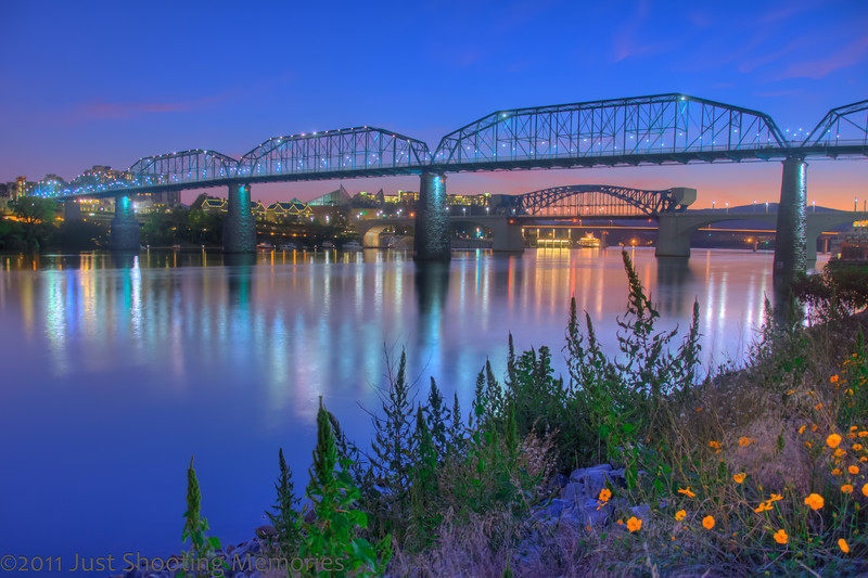 """Back to normal, if anything can be called normal for me. I hope to be able to make posts on time. For anyone new: on time = midnight eastern standard time. Also, don't forget to click on the photo to see it large in Flickr. <h3><strong>Today's Photo: Chattanooga Skyline at Dusk</strong></h3> So, during our few day's off, I was able to sneak a few hours around sunset and then late at night. I was able to make my way across the wonderful pedestrian bridge over the Tennessee River and to Coolidge Park just before sunset. I used my trusty LightTrac iPhone app to find a likely spot with the best angle. I couldn't have planed it better. I had company. In fact there were several people and at least one other photographer in the same area I had chosen. I sat around taking photos through the magic hour and captured this just before I left.  I have been to many cities in the United States, unfortunately none outside, and I must say, Chattanooga has been the most friendly. Everywhere you look at night, it is lit up. Most other cities, when you look down that alley's from the main drag, it is dark. In Chattanooga, you can look for blocks in any direction and it is lit. There was so much here, that I will be back on a regular basis.  Read more at the <a href=""""http://justshootingmemories.com"""">Daily Photography Blog</a> Just Shooting Memories!..."""