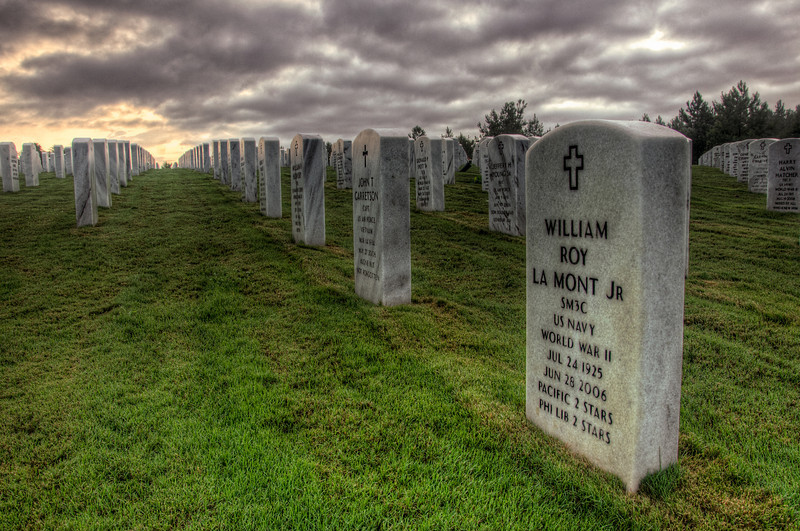 """<h3 style=""""text-align: left;""""><strong>Today's Photo:  Who's Your Hero</strong></h3> <strong></strong>This past weekend, I decided to try to get some sunrise shots at the Georgia National Cemetery.  I was excited, got up early and hoped for the best lighting possible.  What I got instead was not what I was after.  It rained heavy the night before and as I rolled out, the fog was heavy, but I could still see the stars winking from behind clouds.  As I drove, I ran through patches of fog and clear all the way to the entrance of the cemetery.  Then the fog got so heavy I had to slow down considerably.  There was a great calm across the cemetery and with the fog, it weighed that much greater.  Since this is relatively new cemetery, there are not many graves occupied.  However, I would have to say, there were too many with a date of death much too close to a date of birth.  Walking among the headstones, I had so many feelings.  I could almost feel the heavy burden that was borne by these soldiers, but mixed with the calm of the morning created a feeling of peace that I have rarely felt before.  Whether you agree with what our nation fights for or not, you have to respect these men and women that have taken a stand for the freedoms we enjoy.  Walking among these headstones reminds me that the price for freedom is not free.  Our country was built by the hands of men and women like these and its history books written with the blood that ran in their veins.  God Bless these protectors for they bear a burden the rest of us don't.  Read more at the <a href=""""http://justshootingmemories.com"""">Daily Photography Blog</a> Just Shooting Memories!..."""