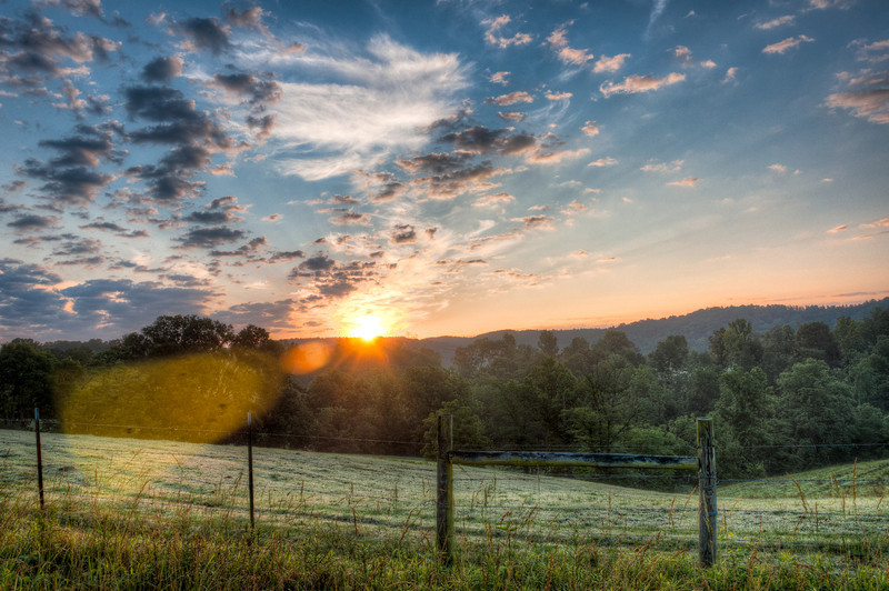 "<h3><strong>Today's Photo:  Country Sunrise</strong></h3> I have the good fortune to live in a place that has several good shots for the sunrise.  This happens to be one of them.  The sunrise here can be very beautiful particularly when there is fog in the valleys.  The morning of this photo, the fog was not real good, but the clouds were stunning. I had a few minutes to devote to photography and this is the result.  Hopefully there will be many more sunrises like this over the summer.  Read more at the <a href=""http://justshootingmemories.com"">Daily Photography Blog</a> Just Shooting Memories!..."