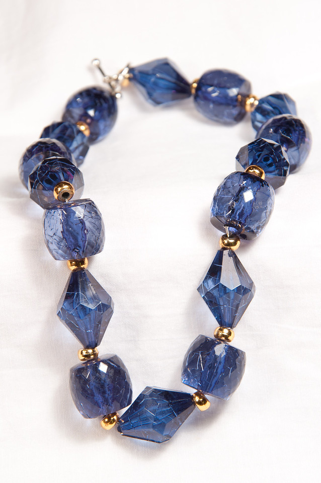 """<p style=""""text-align: center;""""><a title=""""The Blue Bracelet"""" href=""""http://justshootingmemories.smugmug.com/Website/justshootingmemories/19921081_Tt7rDV#!i=1689240599&k=S6pP755&lb=1&s=A""""><img title=""""The Blue Bracelet"""" src=""""http://justshootingmemories.smugmug.com/photos/i-S6pP755/0/XL/i-S6pP755-900x900.jpg"""" alt=""""The Blue Bracelet"""" /></a></p>  <h3><strong>Today's Photo: The Blue Bracelet</strong></h3> At Thanksgiving I learned that one of my relatives has started making jewelry. I was asked to take a few photos and must confess that I had never thought of jewelry photography. I had zero information about the how and no special equipment. I was just armed with a knowledge of the fundamentals of photography. With the help of my wife, we found two backgrounds. One light and one dark. I set up the tripod, a desk lamp and a place to layout the jewelry. After messing with the white balance, I finally settled on one that got rid of the yellow and orange of the incandescent.  I took lots of photos and then put them into Lightroom. AlmostimmediatelyI discovered that I had erred in some of the photos. Now, how to make them work. The photos on the white turned out splendid. The black, not so much. It turns out that my camera takes photos of exactly what I told it to. Which happened to include the fabric pattern of the background cloth.  I processed the light colored background and then began trying to figure out how to salvage the dark. After much thought and trail and error, a light bulb went on (and it was not a flash). Enter Dodge and Burn. I was able to Burn the photo around the background which flattened the fabric pattern almost all the way. Tossed into the bottom here is a before and after of the Burn process.  Read more at the <a href=""""http://justshootingmemories.com"""">Daily Photography Blog</a> Just Shooting Memories!..."""