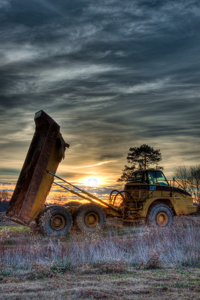 "<h3><strong>Today's Photo:  Dumping the Sunrise</strong></h3> Unfortunately, with today's economy, this has become an all to familiar sight and I think Georgia has caught a lot of this due to our speculative housing boom.  But, this inactivity of lots of heavy machinery makes for some interesting subjects.  I took this shot last winter at sunrise.  I think I was drawn to it by the many geometric shapes you can make out of the elements of the photo.  There were endless possibilities here.  I could have spent hours, but alas the sunrise was too fleeting.  Read more at the <a href=""http://justshootingmemories.com"">Daily Photography Blog</a> Just Shooting Memories!..."