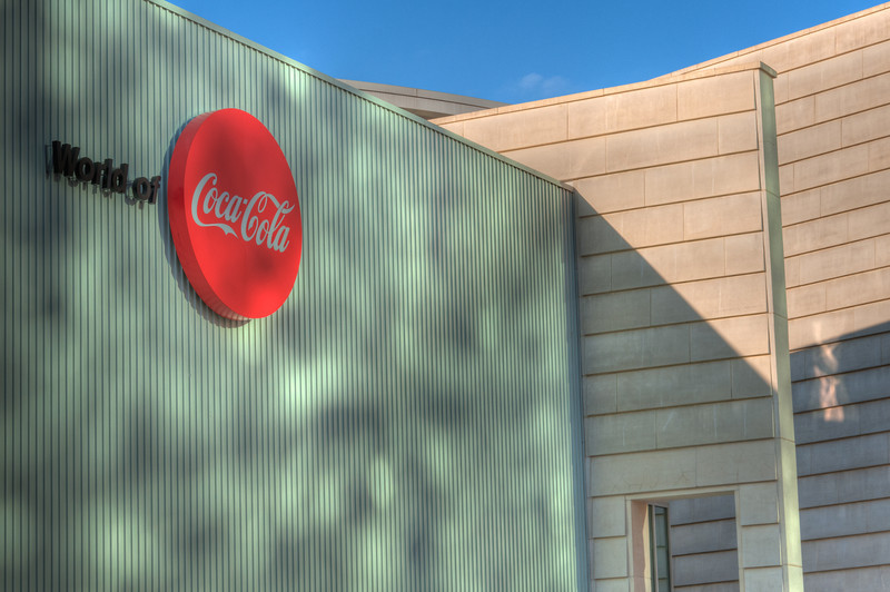 "<h3><strong>Today's Photo:  World of Coke</strong></h3> Coke is one of the worlds oldest soft drinks.  So, it would not be to hard to assume that somewhere there would be a World of Coke.  I mean, there is a ""world"" for everything and the ""world"" for Coke is in downtown Atlanta.  It is just on the outskirts of Centennial Olympic Park.  Several months ago, I got to spend about an hour going through the park and got this shot of the outside of the World of Coke.  What was even more fun was that one of the people I went through the park with decided to run through the spouting water jets.  I guess I need to mention that it was January.  That was kinda funny.  Read more at the <a href=""http://justshootingmemories.com"">Daily Photography Blog</a> Just Shooting Memories!..."