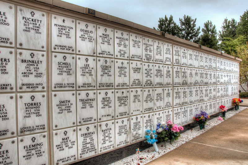 <h3><strong>Today's Photo:  The Columbaria</strong></h3> The Georgia National Cemetery is located just west of Canton Georgia.  It is situated on top of a hill overlooking Lake Allatoona and with a descent view of the east and sunrise.  My goal several weeks ago was to get some sunrise photos at the cemetery.  So, I got up early and drove through the dark to get there.  When I got there, it was just as dawn was beginning.  The fog was extremely heavy near the entrance of the cemetery and it was eirie to drive through.  As I was taking the road around, out of the fog came these rows of walls.  They were not very wide, certainly not enough for a full body, but long.  I stopped by after the fog lifted just to see what it was.  Each of the Columbaria had row after row of names.  Not just any names, but the names of brave soldiers who served this great country.  Many have given some; Some have given all.