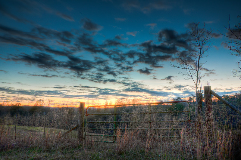 "<h3><strong>Today's Photo:  Sunset at the Gate</strong></h3> I missed the sunset the other day, but I was able to make it to a good spot for some shots just after.  The sun was way below the horizon and just the smallest color was glowing like a line and the clouds were really moving across the sky.  I took my first shots before noticing how fast the clouds were moving.  I changed settings to get a good long exposure and have the clouds moving to get this shot.  The bright star near the middle is actually Venus.  Read more at the <a href=""http://justshootingmemories.com"">Daily Photography Blog</a> Just Shooting Memories!..."
