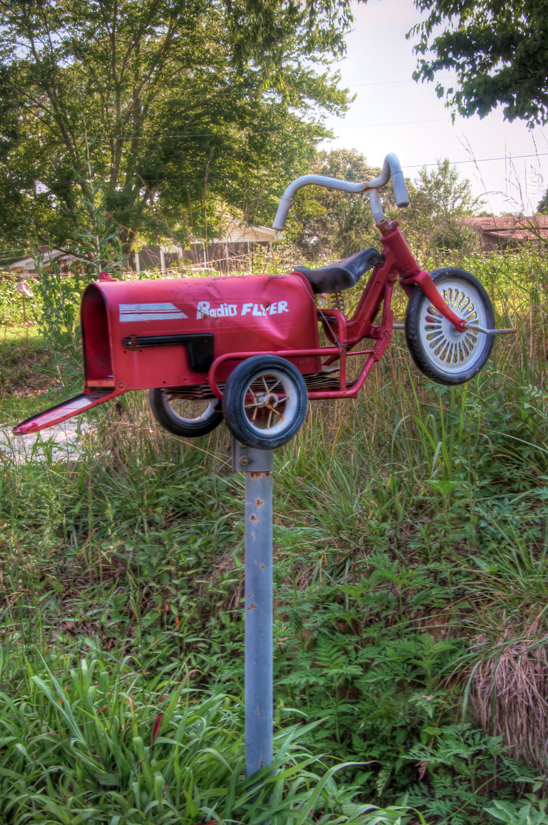 "<h3><strong>Today's Photo:  Radio Flyer</strong></h3> I have no clue what made the Radio Flyer wagon such a popular thing when I was younger.  I guess, at the time, it was the only mode of heavy transportation for children.  You could haul anything in it.  I was driving around a while back when I ran across this mailbox.  Not quite a wagon, but I believe they would have had a problem with soggy mail if they tried to keep to the tradition.  Read more at the <a href=""http://justshootingmemories.com"">Daily Photography Blog</a> Just Shooting Memories!..."