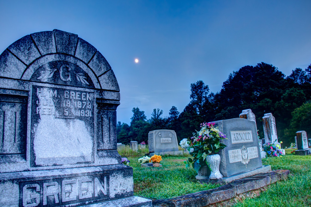 "<h3><strong>Today's Photo:  Tomb Stone</strong></h3> I was driving around one evening just after the sunset when I ran across this graveyard.  It was not very large, but kinda creepy.  The moon was just above the trees and made for a good composition.  I may go back and take some more photos, but I will have to make sure I take some ghost hunting equipment with me too.  Read more at the <a href=""http://justshootingmemories.com"" rel=""nofollow"">Daily Photography Blog</a> Just Shooting Memories!..."