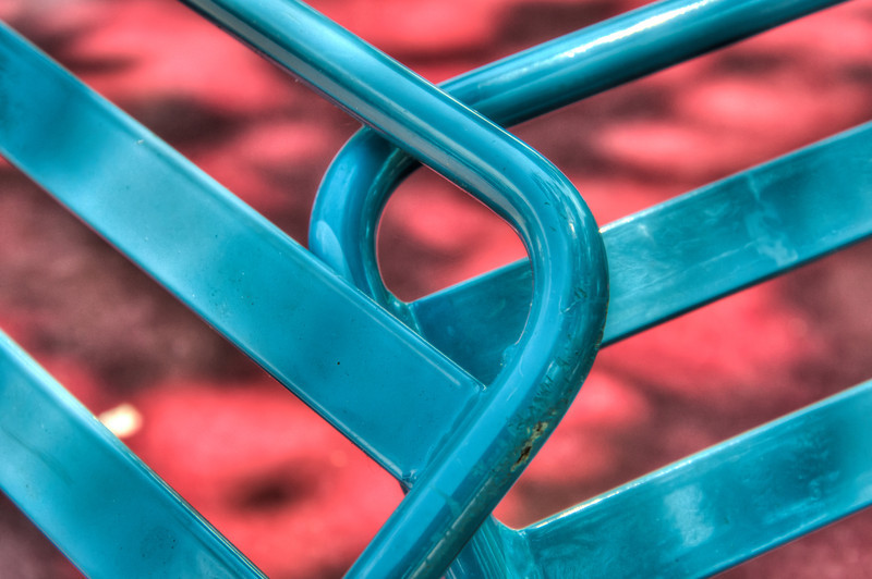 """<h3><strong>Today's Photo: Red and Blue</strong></h3> It has been a while since I went on an expedition to """"Find the small things"""". When I was in Chattanooga this past time, I decided to try several different things. One was some dedicated portrait photography and another was working on my series of finding the small things. I find myself too busy much of the time to slow down and look around at the little picture and not the massive landscapes. I found these chairs in Coolidge Park leaning against their tables. I thought the colors and patterns were complimentary.  Read more at the <a href=""""http://justshootingmemories.com"""">Daily Photography Blog</a> Just Shooting Memories!..."""