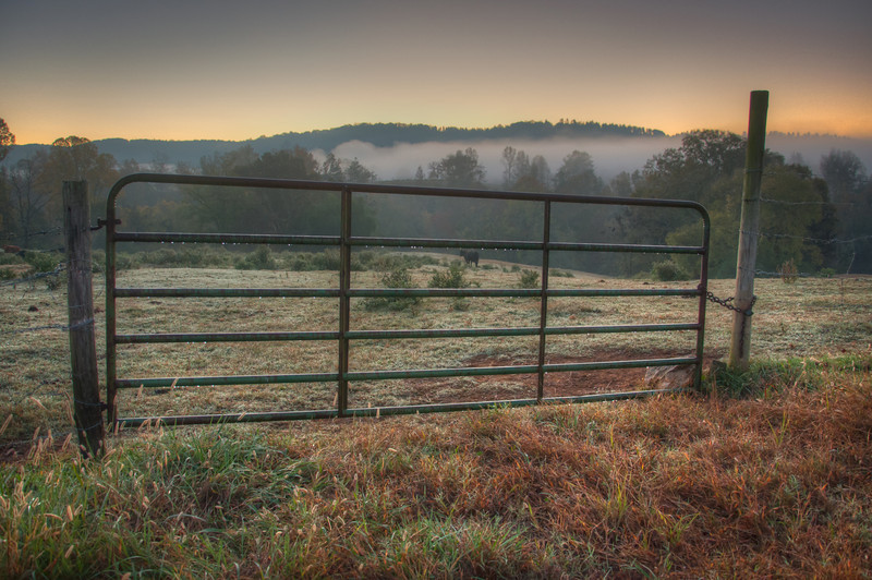 """<h3 style=""""text-align: left;""""><strong>Today's Photo:  Dew Before Dawn</strong></h3> <strong></strong>Sometimes it feels good to get back to the beginning.  Over the last several months, my schedule has not allowed me to be out and about around sunrise or sunset.  This was probably the closest I was in that time frame and it was still several minutes off.  However, I really liked the dew on the gate and the fog visible in the distant valleys.  Maybe the next few months will allow me some sunrise time, or maybe I will just have to schedule it.  It seems everything I do these days has to be scheduled."""