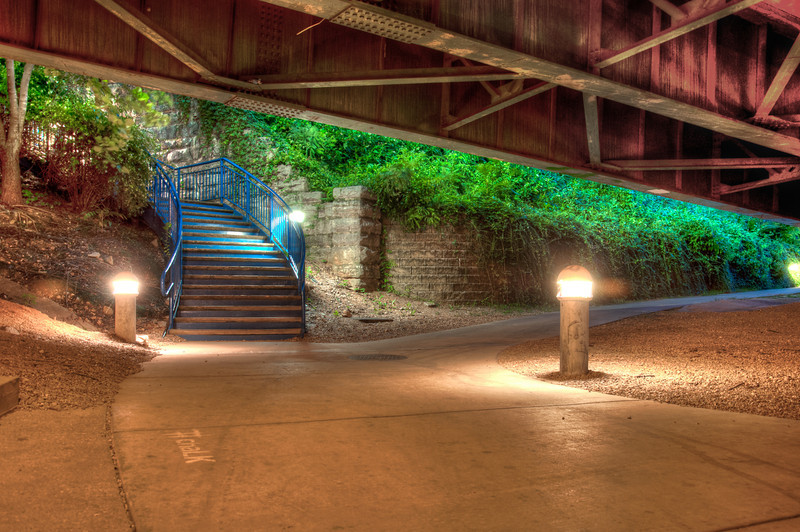 """<h3 style=""""text-align: left;""""><strong>Today's Photo:  Where to go Next</strong></h3> It is nice when a city becomes really involved in development that is meant to attract people to continue to explore.  That is the feeling I get every time I visit Chattanooga.  No matter where I go, there is that feeling that I need to keep going to see what is around the next corner.  There are many paths like this one where you can not see where they lead, but all of them are enticing.  Do you take the stairs or the path?  Maybe you turn around and go down the steps behind you, or up the <a title=""""Endless Turns"""" href=""""http://justshootingmemories.com/2012/09/18/endless-turns/"""">Endless Turns</a>?  No matter which way, there is always something interesting to see."""
