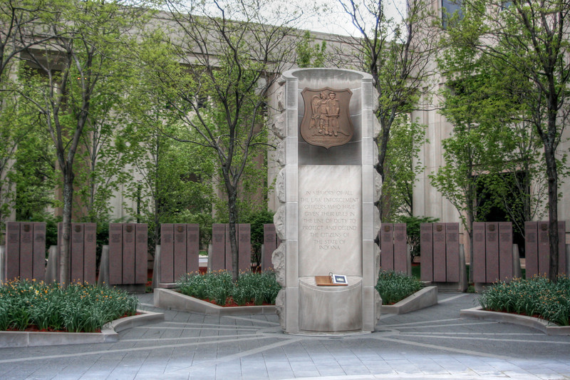 "<h3><strong>Today's Photo:  St. Michael Archangel (Indiana Law Enforcement Memorial)</strong></h3> Situated just outside the Indiana capital building is sacred ground to a group of public safety.  This is the location of the Indiana Law Enforcement Memorial.  Inscribed on the columns behind the main monument are the names of all the officers who have given their lives in the line of duty.  Stepping into this circle, I seemed to be surrounded by a quiet, even though just a short way away is the center of a bustling city.  It is a sobering moment to spend inside this circle of heroes.  Read more at the <a href=""http://justshootingmemories.com"">Daily Photography Blog</a> Just Shooting Memories!..."