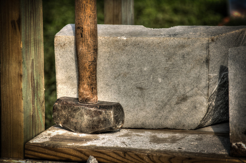 """<h3 style=""""text-align: left;""""><strong>Today's Photo:  The Stone Carvers Hammer</strong></h3> Like """"leaf lookers"""", I used to be one of the people who avoided craft shows and festivals at all costs.  I think it was due to my time living in the small North Georgia town of Ellijay and enjoying the gridlock and frustration for two weekends in October every year for the Apple Festival.  I would make it a point to disappear those weekends.  However, I have been getting lax in my dislike of these shows and actually go to a few of them each year.  Usually even the dreaded Apple Festival.  I made it to the Marble Festival in Jasper Georgia a couple of weeks ago.  Although no where near as large as the Apple Festival, it was still a nice show and a little more manageable time wise.  We were walking down one of the aisles of tents when I ran across a guy carving a large block of marble.  It was fascinating to see him switch from powered tools to small pieces of rock and chisels and watch the marble slowly melt away and the form of a knight kneeling and kissing the hand of a lady begin to appear.  Under the table, waiting for the right time, was his hammer.  Just the thing for those delicate touches."""