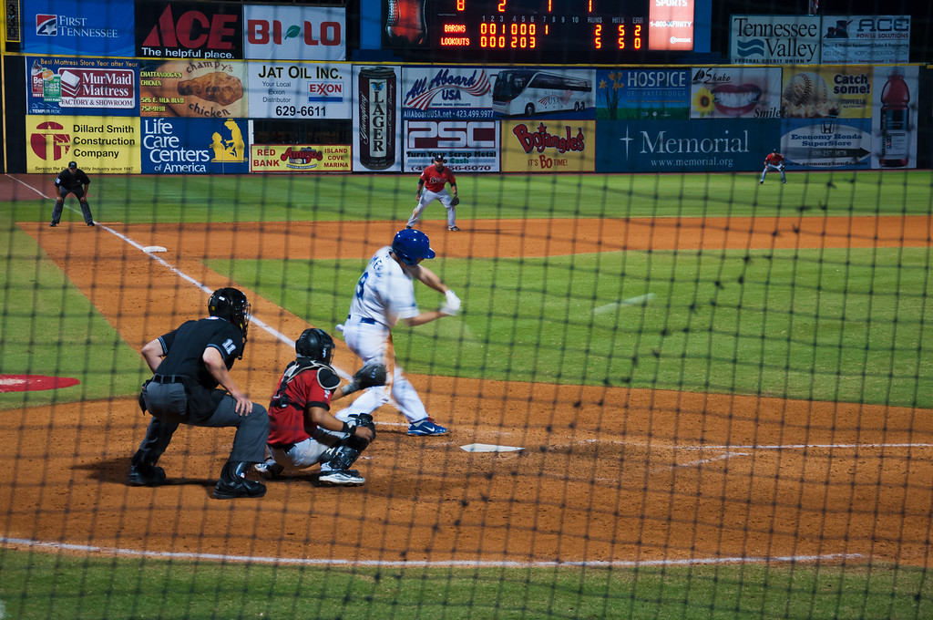 """<h3><strong>Today's Photo: Chattanooga Lookouts</strong></h3> Several weeks ago, I went to Chattanooga for a day with the family. We decided to go on a weekday and try to miss the crowds. As usual, we made it around lunch time and went exploring downtown for a good bite. One of therestaurantswe went past had a sign that said we could get free tickets to the Chattanooga Lookouts baseball game. We decided on a different place, thinking we would not be there late enough. However, we hung out until dinner and I got a wild bug to check prices for seats. Nothing like the minors for a cheap ticket. We spent about $35.00 and sat almost directly behind home plate. I got some good shots, but I wish we had been more around the area of the dugout. Otherwise, what a fun time for pennies compared to just about anything else we could have done.  Read more at the <a href=""""http://justshootingmemories.com"""">Daily Photography Blog</a> Just Shooting Memories!..."""