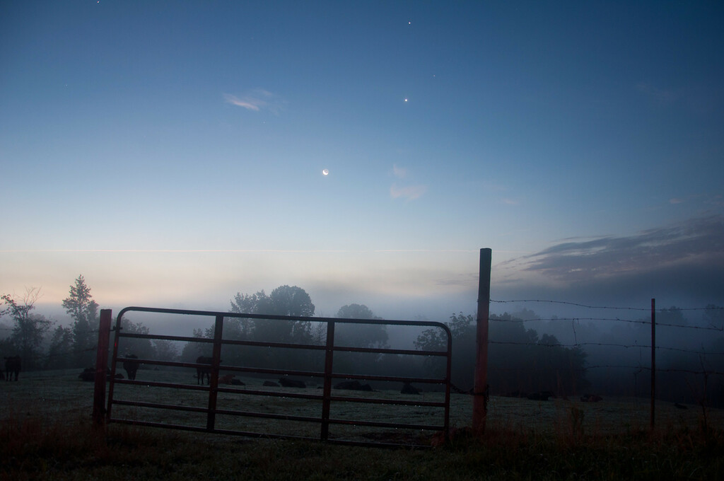 "<h3><strong>Today's Photo:  Jupiter, Venus and the Moon</strong></h3> I held on to the dream of being an astronaut for many years after all my peers had moved on.  In fact, I still have that passion for outer space, just the knowledge that I will probably not get to feel the weightlessness of orbit.  I can still enjoy looking up at the stars and thinking what it may be like to walk among them.  I really enjoy the early morning hours when the stars are still out, yet the sun is brightening up the sky enough to see the landscape.  I watched this develop for several days before getting the right line up of Jupiter, Venus and the Moon.  Read more at the <a href=""http://justshootingmemories.com"">Daily Photography Blog</a> Just Shooting Memories!..."