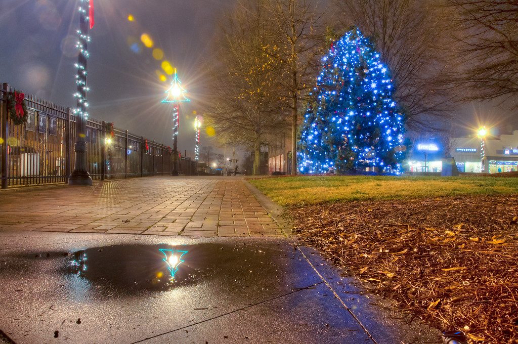 """<h3><strong>Today's Photo: Christmas Reflection</strong></h3> Okay, I could not resist posting another shot of Christmas lights. I was out most of the day on Christmas day. On our way home, we passed through downtown Cartersville after dark and I saw this tree in the middle of town. Having been so busy this December, I have not been able to get out and see a lot of lights like I wanted. So, I decided to stop for a quick shot. While I was walking around, I noticed this little puddle of water off to the side. It made for the perfect reflection.  Read more at the <a href=""""http://justshootingmemories.com"""" rel=""""nofollow"""">Daily Photography Blog</a> Just Shooting Memories!..."""