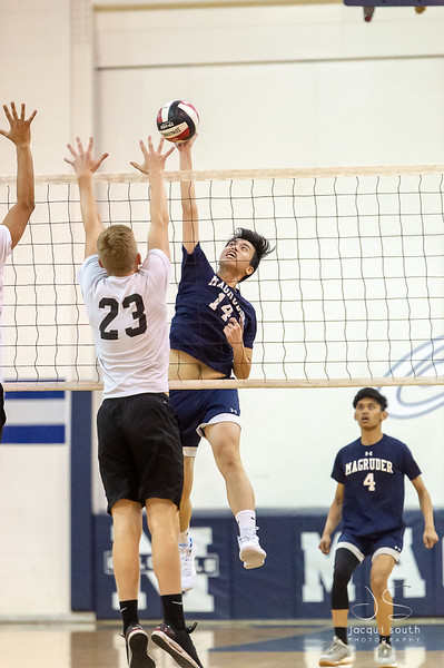 4/2/2019 - Alexander Willis (23) for Blake HS goes up to block this shot by Magruder's (14). Magruder Boys Varsity Volleyball, ©2019 Jacqui South Photography