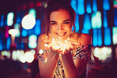 Beautiful young woman smiling and talking garlands of lights at city