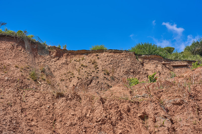Erosion; note the remains of a road at the top of the cliff.