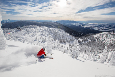A skier in deep snow on the North Bowl at Whitefish Mountain Resort. with Glacier National Park in the background.