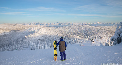 A snowbaorder looks over Glacier National Park at Whitefish Mountain Resort.