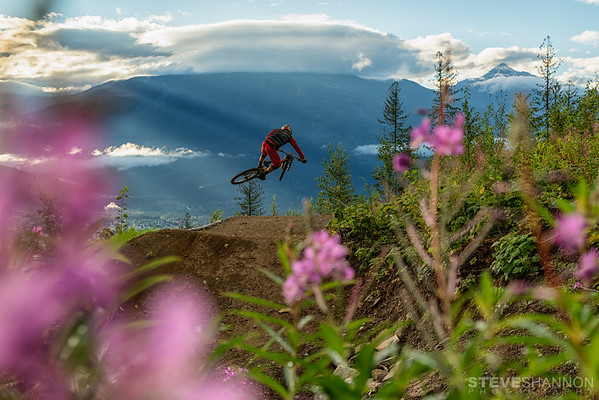 Luke Stevens jumping his mountain bike on the Rooster Trail above Revelstoke, BC with Mount Mackenzie and Cartier in the background.