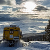 A snowcat descends from Meadow Mountain above the clouds over Kootenay Lake at Selkirk Wilderness Skiing near Meadow Creek, British Columbia.