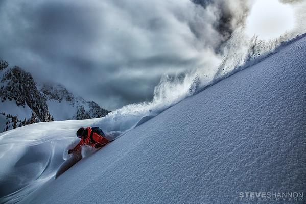 A heli skier enjoys deep powder skiing with Stellar Heli Skiing on Mount Brennan near Kaslo, British Columbia.