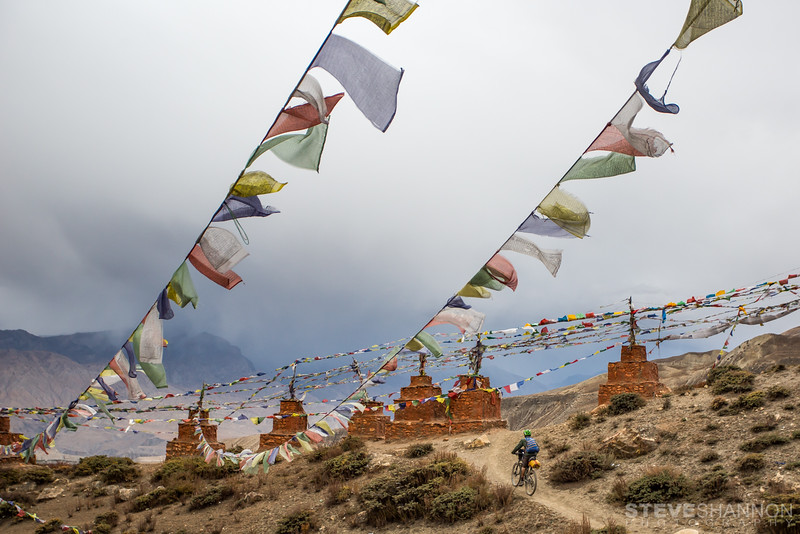 The Chortens and Gompas of the Mustang region are truly spectacular.  This shot was taken just as we left Ghar Gompa, one of the oldest Tibetan gompas in the world.  Using the leading lines of the prayer flags to frame the trail, I waited for some tourists to move along then Todd quickly pedalled up the trail.