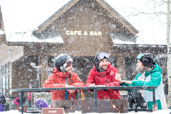Three people around the fire pit at the Base Lodge at Whitefish Mountain Resort.