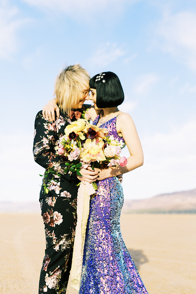short hairstyles for rad brides - Las Vegas dry lake bed elopement at sunrise - yellow peony bridal bouquet with purple ranunculus - multi-colored, sequin, fitted, unconventional wedding gown and deep plum floral suit - colorful, artistic, and unconventional desert elopement inspiration - Kristen Krehbiel - Kristen Kay Photography - Las Vegas Wedding and Elopement Photographer