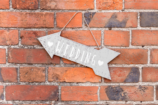 Wedding Sign on Wooden a Arrow Against a Red Brick Wall