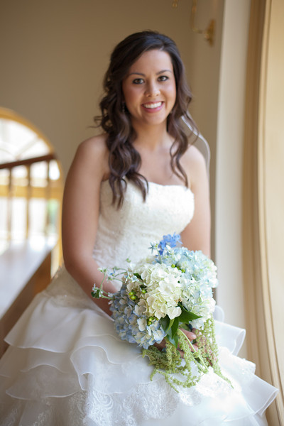Alex sits for a bridal portrait by the round windows at the American Village chapel. Wedding bouquet by Lillie's. Daniel Taylor Photography