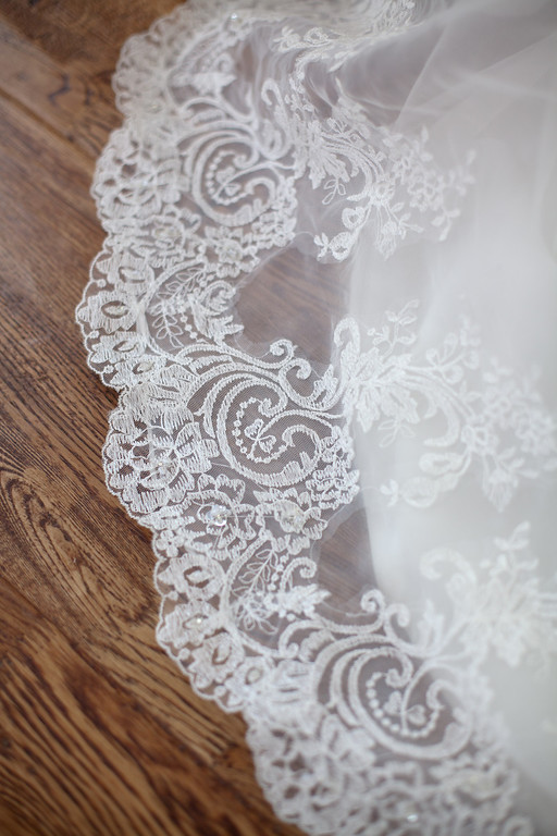 The intricate lace of Alex's wedding dress. Photographed at American Village by Daniel Taylor Photography.