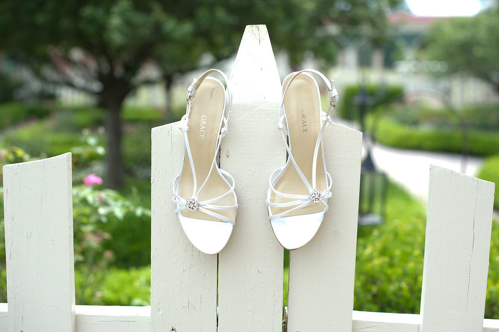 Alex's wedding shoes hang on the white picket fence at American Village. Daniel Taylor Photography