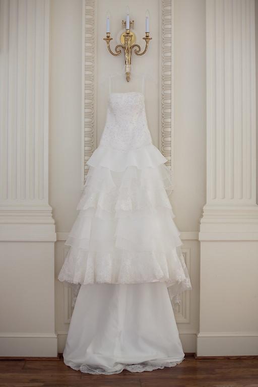 Alex's stunning wedding dress hangs in the ballroom at American Village. Daniel Taylor Photography