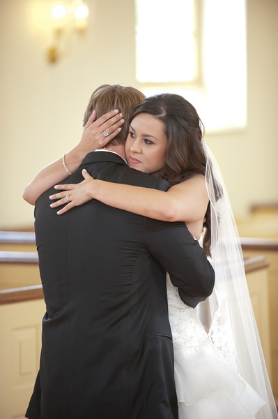 The bride and groom hug in the chapel at American Village. Daniel Taylor Photography