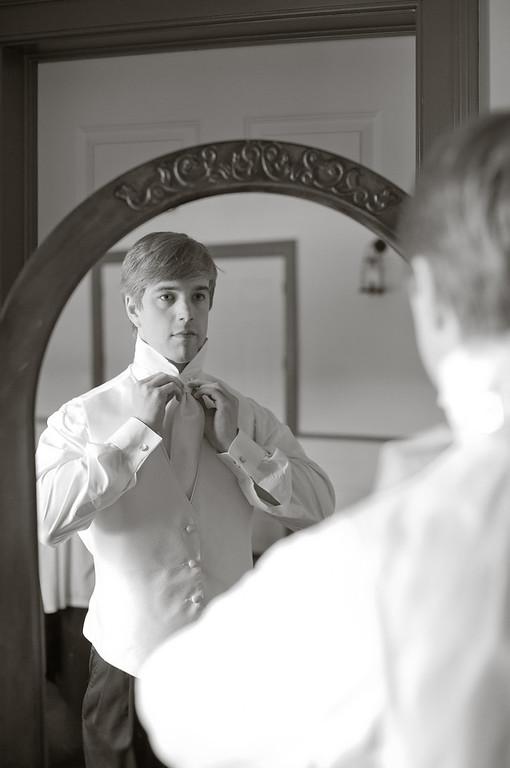 Groom Ben ties his tie before the wedding. Daniel Taylor Photography at American Village.