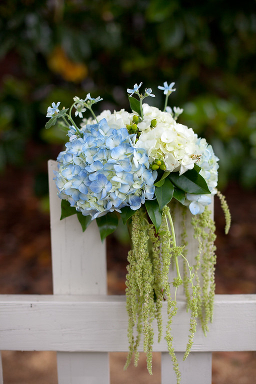 A beautiful romantic wedding bouquet by Lillie's, in green, blue and white on the fence at American Village. Daniel Taylor Photography