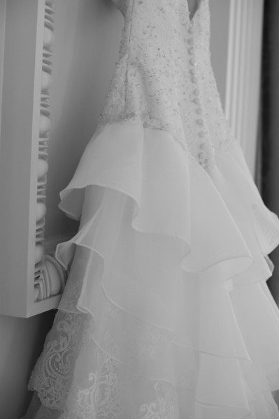 In black and white: A side view of the wedding dress hanging in the American Village ballroom. Daniel Taylor Photography