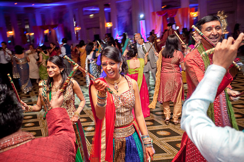 """Everyone enjoys doing """"raas""""-a traditional Gujurati folk dance involving sticks during this traditional Hindu engagement ceremony. Daniel Taylor Photography"""