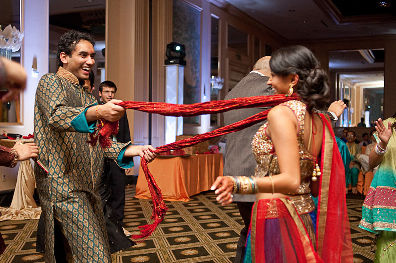 A fun dance with the dupatta scarf during the Hindu engagement celebration at Wynfrey Hotel in Birmingham, Ala. Photo by Daniel Taylor Photography