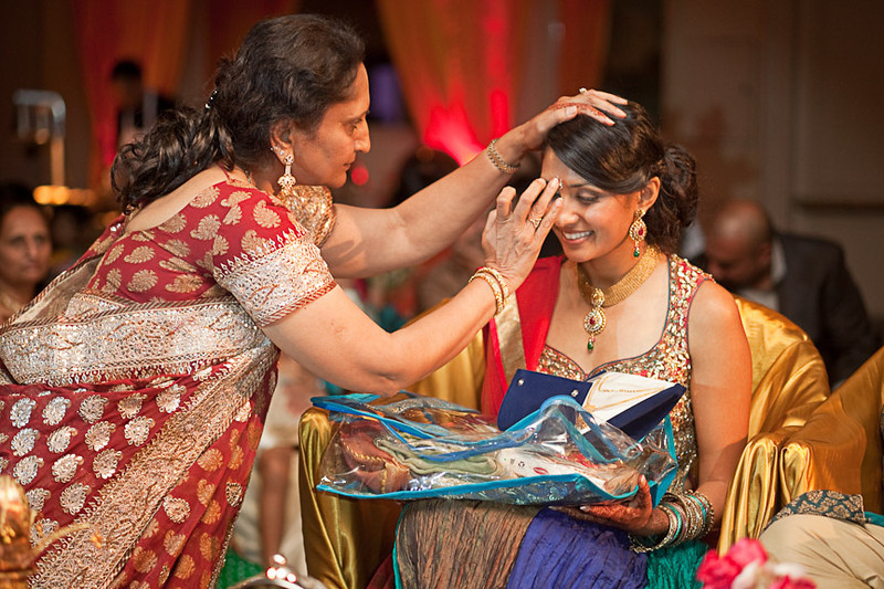 """The groom's mother applies a """"chandlo"""" or """"tilak"""" to her daughter-in-law-to-be during the Hindu Engagement ceremony. Daniel Taylor Photography"""